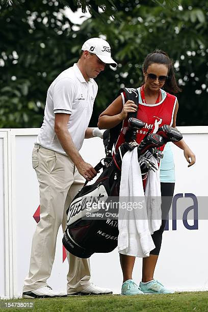 Nick Watney of USA helps his wife Amber Watney put on the golf bags during the ProAm ahead of the CIMB Asia Pacific Classic at The MINES Resort Golf...