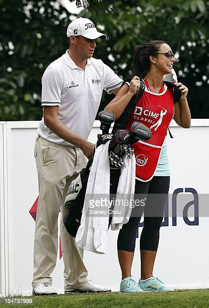 Nick Watney of USA of USA helps his wife Amber Watney put on the golf bags during the ProAm ahead of the CIMB Asia Pacific Classic at The MINES...