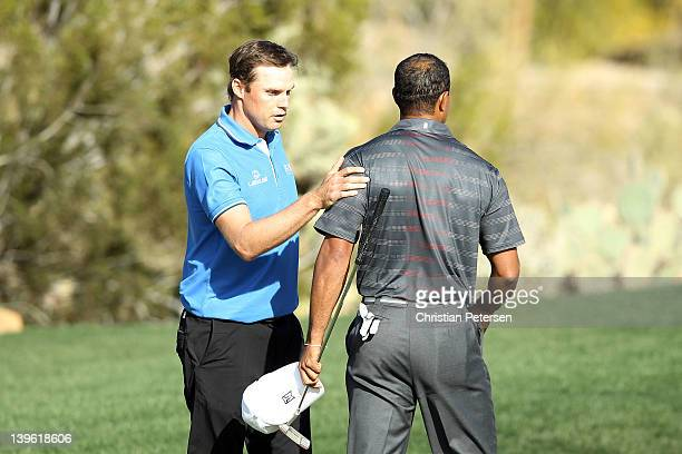 Nick Watney pats Tiger Woods on the shoulder after defeating him to win the match on the 18th hole during the second round of the World Golf...