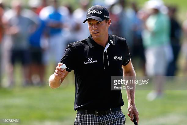 Nick Watney waves his ball towards the fans as he reacts after he made a birdie putt on the first hole during the third round of The Barclays at the...