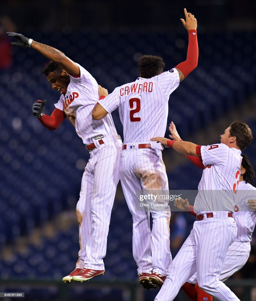 Nick Williams #5, J.P. Crawford #2 and Andrew Knapp #34 of the Philadelphia Phillies celebrate William's walk off RBI double in the 15th inning against the Miami Marlins at Citizens Bank Park on September 12, 2017 in Philadelphia, Pennsylvania. The Phillies won 9-8.