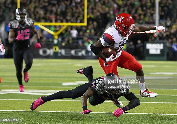Nick Wilson of the Arizona Wildcats breaks a tackle attempt by Ifo EkpreOlomu of the Oregon Ducks to score a touchdown at Autzen Stadium on October 2...