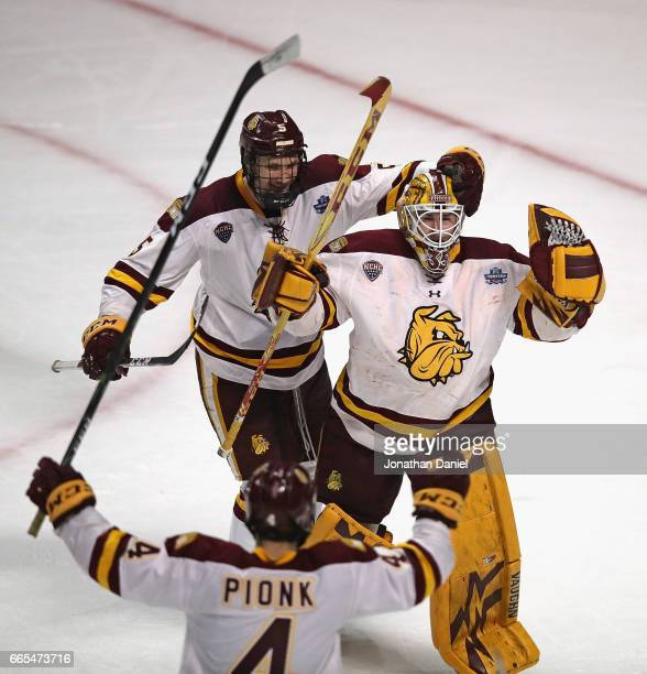 Nick Wolff Hunter Miska and Neal Pionk of the MinnesotaDuluth Bulldogs celebrate a win over the Harvard Crimson during game one of the 2017 NCAA...