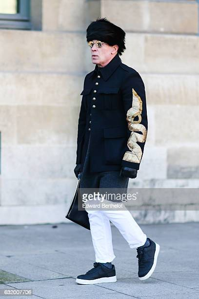 Nick Wooster is wearing a black Russian chapka fur hat sunglasses a navy blue jacket a black clutch white pants and black shoes after the Balenciaga...