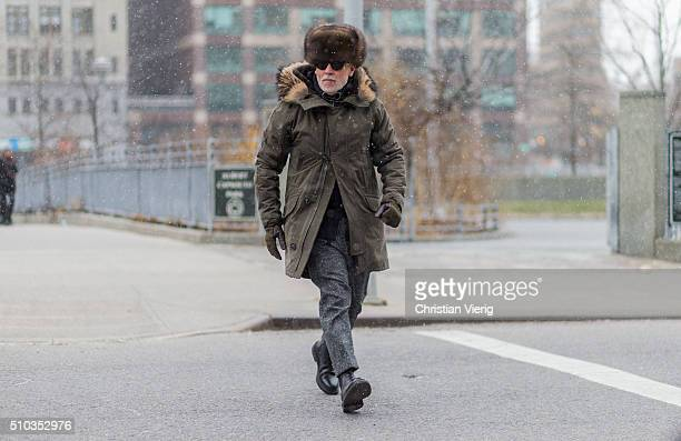 Nick Wooster is wearing a olive parka a fur hat and grey suit pants seen outside Lacoste during New York Fashion Week Women's Fall/Winter 2016 on...