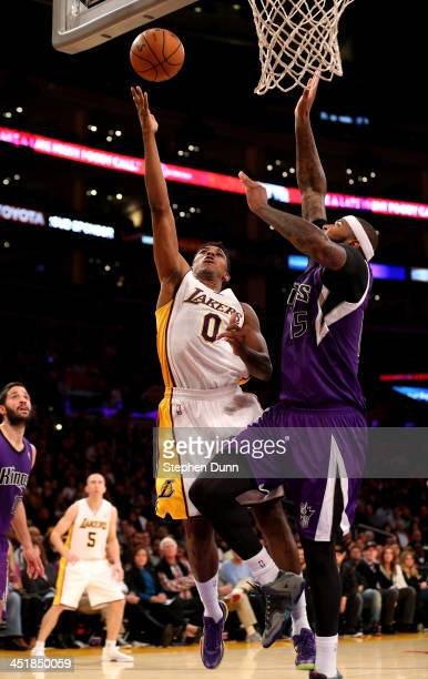 Nick Young of the Los Angeles Lakers shoots over DeMarcus Cousins of the Sacramento Kings at Staples Center on November 24, 2013 in Los Angeles,...