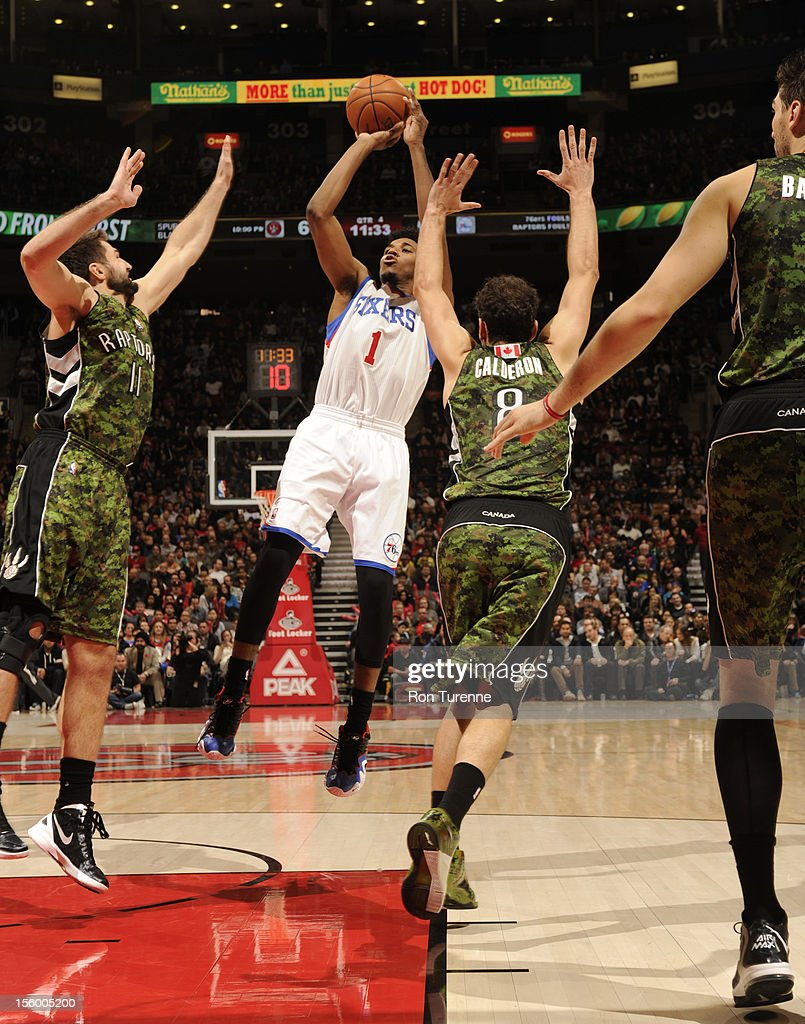 Nick Young #1 of the Philadelphia 76ers shoots the ball over Linas Kleiza #11 and Jose Calderon #8 of the Toronto Raptors during the game on November 10, 2012 at the Air Canada Centre in Toronto, Ontario, Canada.