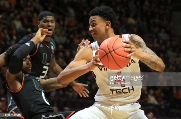 Nickeil AlexanderWalker of the Virginia Tech Hokies looks to run while being guarded by Chris Likes and Anthony Lawrence of the Miami Hurricanes at...