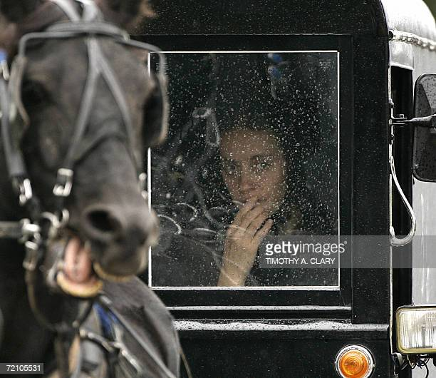 A young Amish woman peers out the window of a buggy in the funeral procession of Anna Mae Stoltzfus age 12 a victim of the Amish School shooting as...