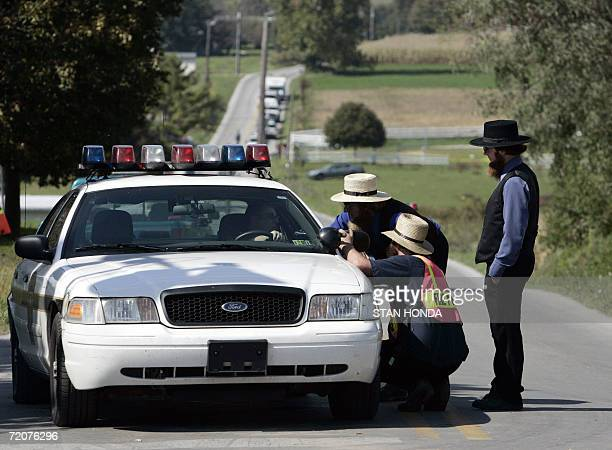 Amish men speak with a police officer on a road leading to the oneroom West Nickel Mines Amish School 03 October 2006 in the town of Nickel Mines...