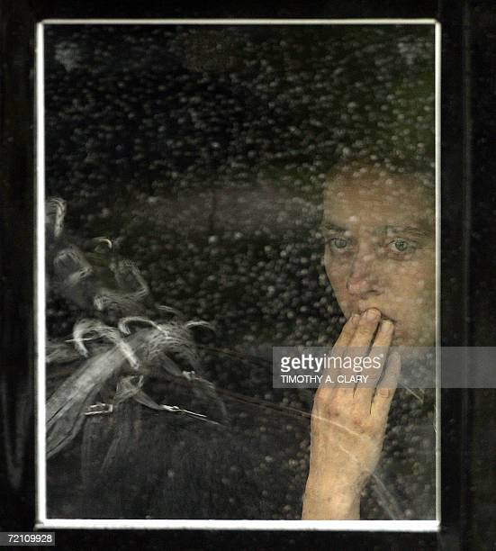 An Amish woman peers out the window of a buggy in the funeral procession of Anna Mae Stoltzfus age 12 a victim of the Amish School shooting as it...