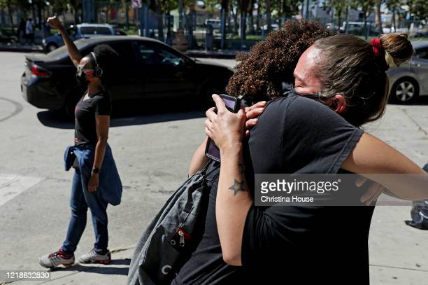 Nickey Bennett right receives a hug from her daughter Roxi Reed after becoming emotional while watching a procession depart Leimert Park for downtown...