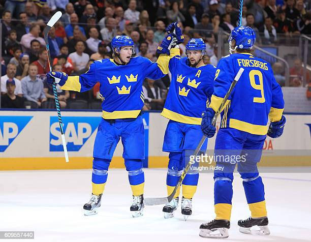 Nicklas Backstrom celebrates with Erik Karlsson and Filip Forsberg of Team Sweden after scoring a first period goal Team North America during the...