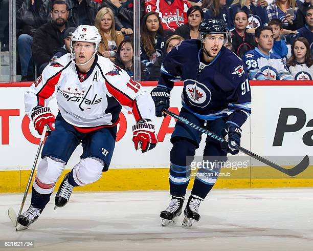 Nicklas Backstrom of the Washington Capitals and Alexander Burmistrov of the Winnipeg Jets follow the play down the ice during first period action at...