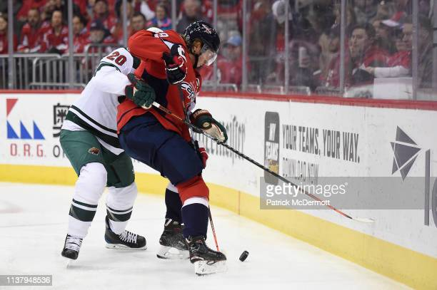 Nicklas Backstrom of the Washington Capitals and Ryan Suter of the Minnesota Wild battle for the puck in the first period at Capital One Arena on...
