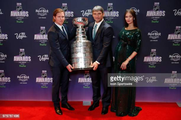 Nicklas Backstrom of the Washington Capitals and teammate Alex Ovechkin with his wife Anastasia Shubskaya pose with the Stanley Cup on the red carpet...