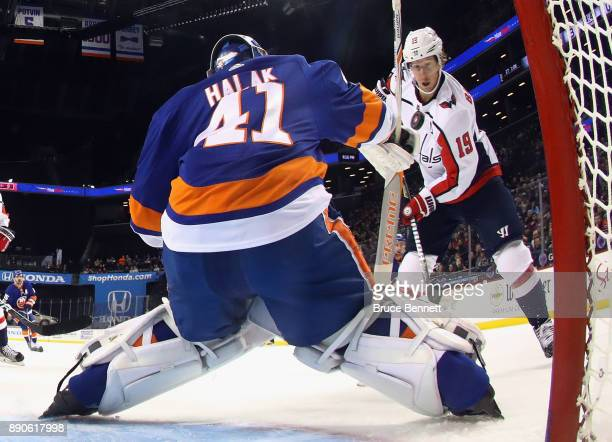 Nicklas Backstrom of the Washington Capitals attempts to control the puck in front of Jaroslav Halak of the New York Islanders during the second...