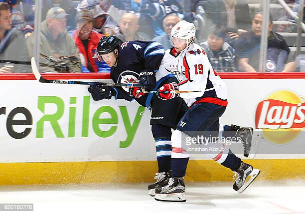 Nicklas Backstrom of the Washington Capitals checks Paul Postma of the Winnipeg Jets into the boards during third period action at the MTS Centre on...