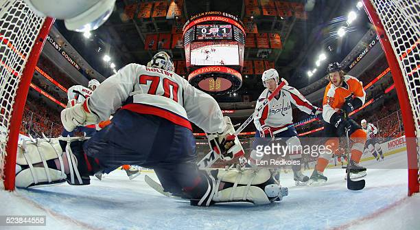 Nicklas Backstrom of the Washington Capitals defends goaltender Braden Holtby against the attack of Ryan White of the Philadelphia Flyers in Game Six...