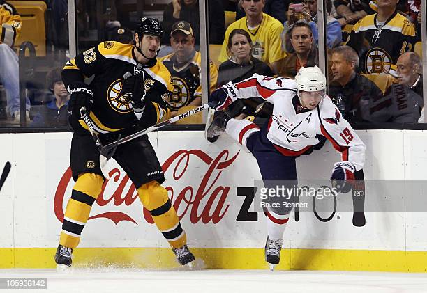 Nicklas Backstrom of the Washington Capitals is tripped up by Zdeno Chara of the Boston Bruins at the TD Garden on October 21, 2010 in Boston,...