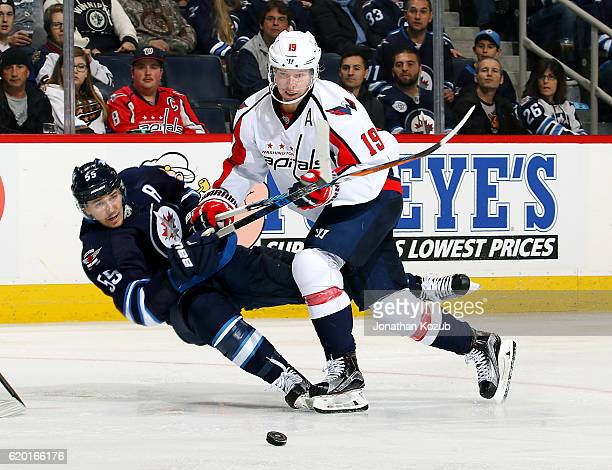 Nicklas Backstrom of the Washington Capitals knocks Mark Scheifele of the Winnipeg Jets to the ice as they battle for the loose puck during second...