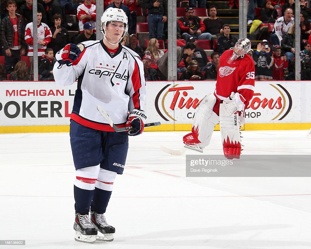 Nicklas Backstrom #19 of the Washington Capitals pumps his fist after scoring the winning goal in a shootout while goalie Jimmy Howard #35 of the Detroit Red Wings skates away during an NHL game at Joe Louis Arena on November 15, 2013 in Detroit, Michigan. The Capitals defeated the Wings 4-3 in a shootout.