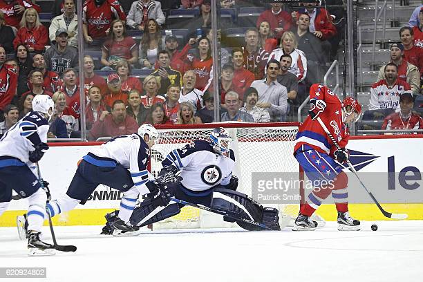 Nicklas Backstrom of the Washington Capitals scores on goalie Michael Hutchinson of the Winnipeg Jets during the first period at Verizon Center on...