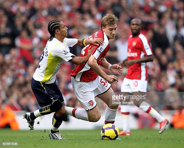 Nicklas Bendtner of Arsenal is challenged by Benoit AssouEkotto of Tottenham Hotspur during the Barclays Premier League match between Arsenal and...