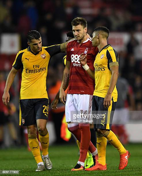 Nicklas Bendtner of Nottingham Forest is consoled by Granit Xhaka and Kieran Gibbs of Arsenal after the EFL Cup Third Round match between Nottingham...