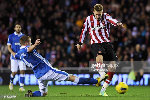 Nicklas Bendtner of Sunderland shoots past James McCarthy of Wigan during the Barclays Premier League match between Sunderland and Wigan Athletic at...