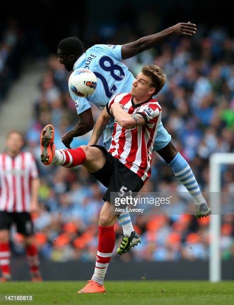 Nicklas Bendtner of Sunderland tangles with Kolo Toure of Manchester City during the Barclays Premier League match between Manchester City and...