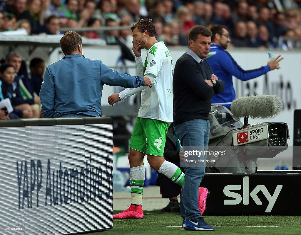 Nicklas Bendtner (C) of Wolfsburg walks past head coach Dieter Hecking (R) after his substitution during the Bundesliga match between VfL Wolfsburg and Hertha BSC at Volkswagen Arena on September 19, 2015 in Wolfsburg, Germany.