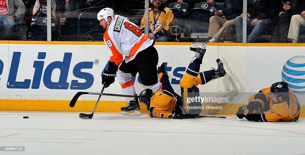 Nicklas Grossmann #8 of the Philadelphia Flyers carries the puck past a fallen Craig Smith #15 and Filip Forsberg #9 of the Nashville Predators during the second period of a game at Bridgestone Arena on December 27, 2014 in Nashville, Tennessee.