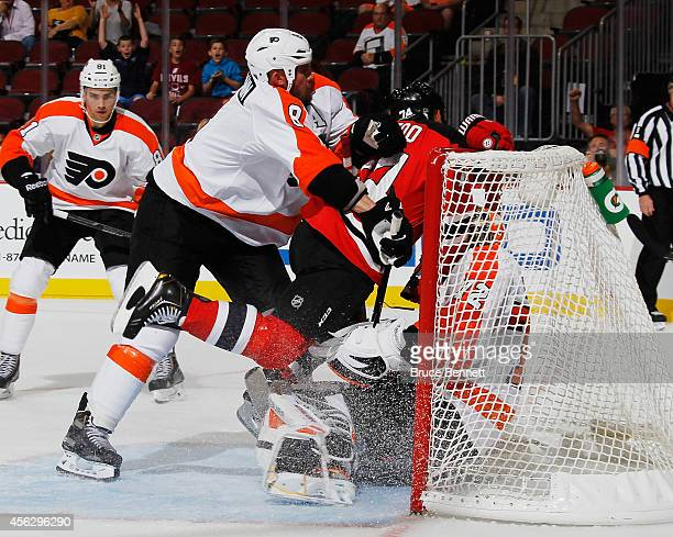 Nicklas Grossmann of the Philadelphia Flyers pushes Jordin Tootoo of the New Jersey Devils into goaltender Rob Zepp during the second period at the...