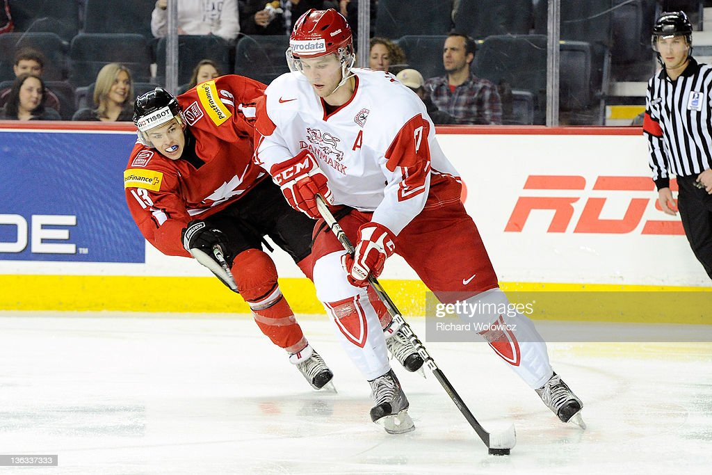 Nicklas Jensen #17 of Team Denmark skates with the puck while being defended by Gregory Hofmann #13 of Team Switzerland during a relegation game at the 2012 World Junior Hockey Championships at the Saddledome on January 2, 2012 in Calgary, Alberta, Canada.