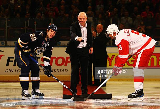 Nicklas Lidstrom of Detroit Red Wings and Alexander Steen of St Louis Blues have a ceremonial faceoff with recently retired player Mats Sundin prior...