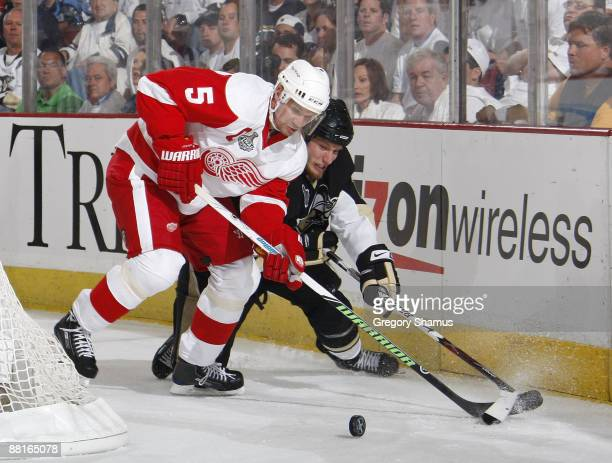 Nicklas Lidstrom of the Detroit Red Wings fights for the puck against Jordan Staal of the Pittsburgh Penguins during Game Three of the 2009 NHL...