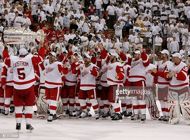 Nicklas Lidstrom of the Detroit Red Wings hands off to Dallas Drake as they celebrate with the Stanley Cup after defeating the Pittsburgh Penguins in...