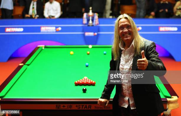 Nicko McBrain drummer for Iron Maiden poses by the table as he watches the final of the World Snooker Championship between John Higgins of Scotland...