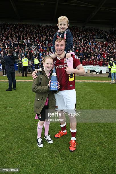 Nicky Adams of Northampton Town celebrate with his family after receiving the Sky Bet League Two champions trophy after Sky Bet League Two match...