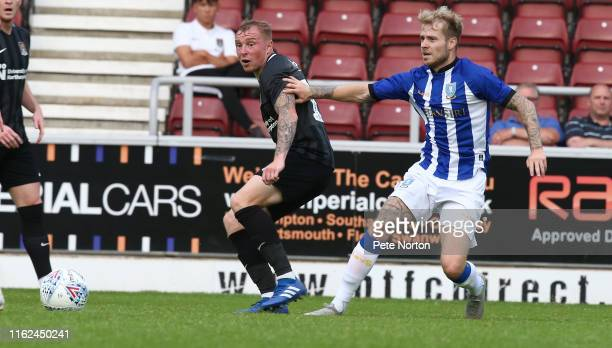 Nicky Adams of Northampton Town plays the ball under pressure from Ashley Baker of Sheffield Wednesday during the PreSeason Friendly match between...