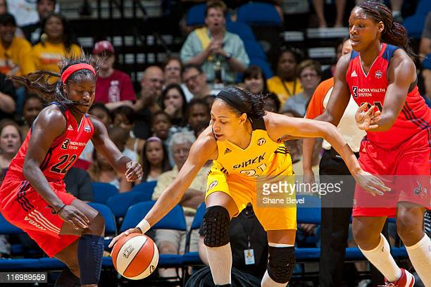 Nicky Anosike and Matee Ajavon of the Washington Mystics watch as Jennifer Lacy of the Tulsa Shock slips between them during the WNBA game on June 18...