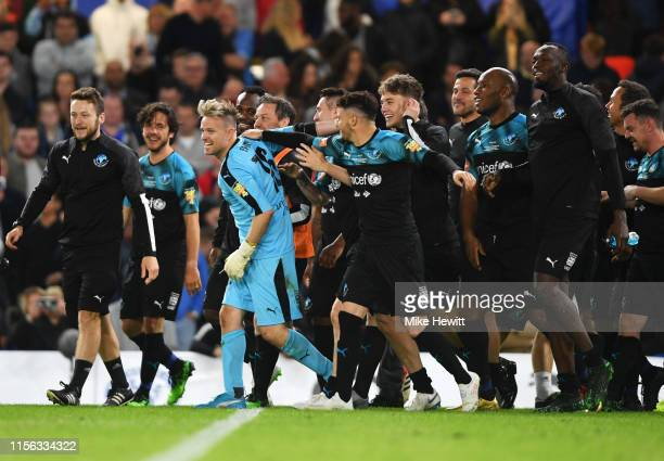 Nicky Byrne of Soccer Aid World XI celebrates with team mates as he saves the decisive penalty in the shoot out from Lee Mack of England to claim...