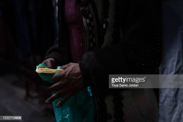 Nicky Castelan holds tortillas as she prepares dinner on a sidewalk in the Buenavista neighborhood on June 21 2020 in Mexico City Mexico Nicky a HIV...