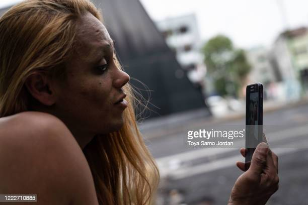 Nicky Castelan talks to her sister by video on a sidewalk in the Buenavista neighborhood on June 21 2020 in Mexico City Mexico Nicky a HIV positive...