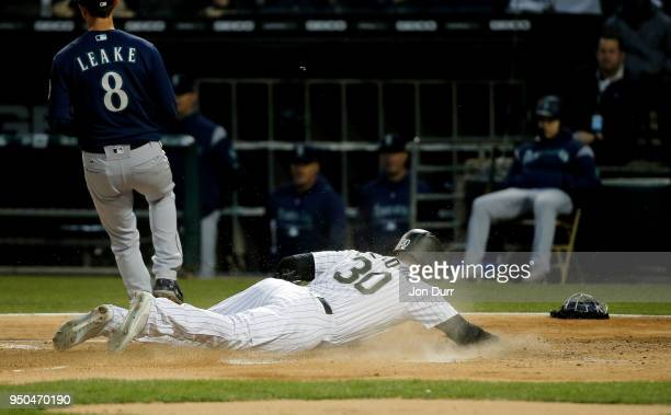 Nicky Delmonico of the Chicago White Sox dives as he steals home after a wild pitch thrown by Mike Leake of the Seattle Mariners during the first...