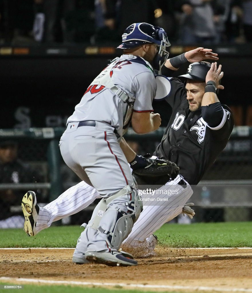 Nicky Delmonico #30 of the Chicago White Sox dives in to score a run in the 6th inning past Chris Gimenez #38 of the Minnesota Twins at Guaranteed Rate Field on August 24, 2017 in Chicago, Illinois.