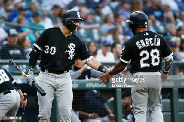 Nicky Delmonico of the Chicago White Sox greets Leury Garcia after he scored in the first inning against the Seattle Mariners at Safeco Field on July...