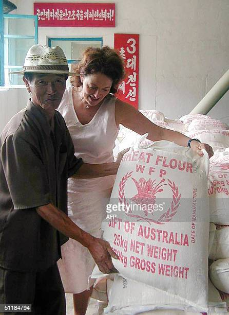 Nicky downer wife of Australian Foreign Minister Alexander Downer along with an unidentified North Korean shows a sack of wheat flour donated by...