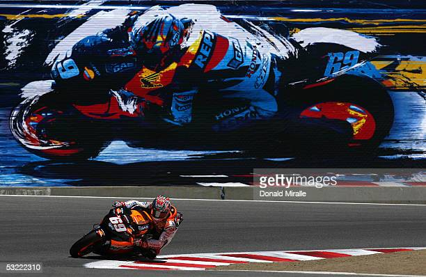 Nicky Hayden of the USA rides his Repsol Team Honda past his likeness on a billboard en route to winning the 2005 Red Bull US Grand Prix part of the...